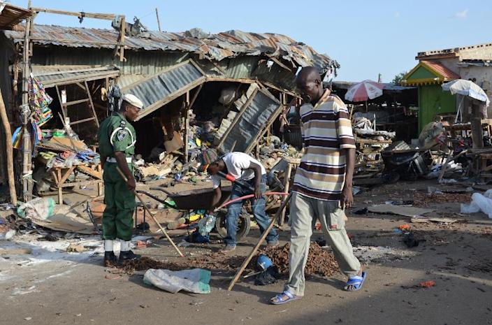 A man walks past a the scene of a bombing after at least 20 people were killed at a bus station in Maiduguri, northeast Nigeria, on June 22, 2015 (AFP Photo/)