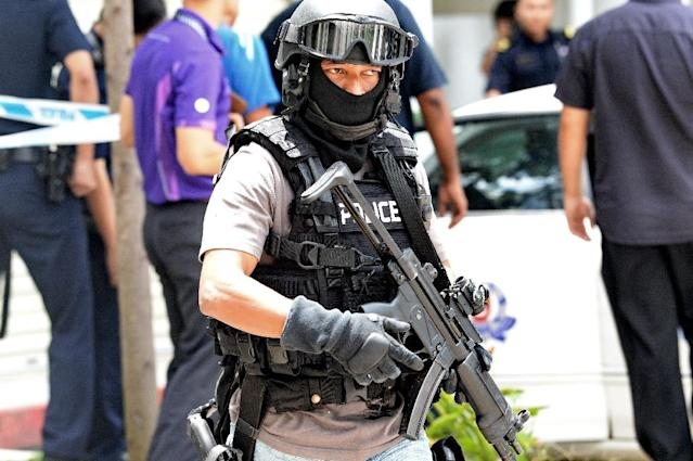 Officers spent close to eight hours at the Football Association of Singapore offices before carting off 18 boxes of documents, an AFP reporter said (AFP Photo/ROSLAN RAHMAN)