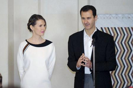 Syria's President Bashar al-Assad stands next to his wife Asma, as he addresses injured soldiers and their mothers during a celebration marking Syrian Mother's Day in Damascus