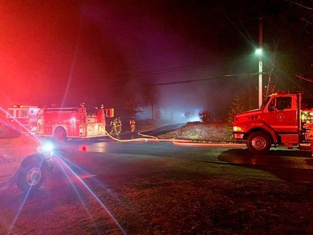 Halifax Fire crews walk towards a house fire on Buckingham Drive in Stillwater Lake on March 26, 2021. A person died in the fire, which was related to a lightning strike.