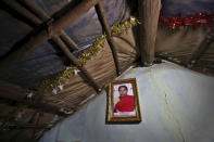 A portrait of Padmavathi, who died of COVID-19, hangs on the wall of her family hut made from bamboo and plastic sheeting in a slum in Bengaluru, India, Thursday, May 20, 2021. Padmavathi collected hair, taking it from women's combs and hairbrushes to later be used for wigs. She earned about $50 a month. (AP Photo/Aijaz Rahi)