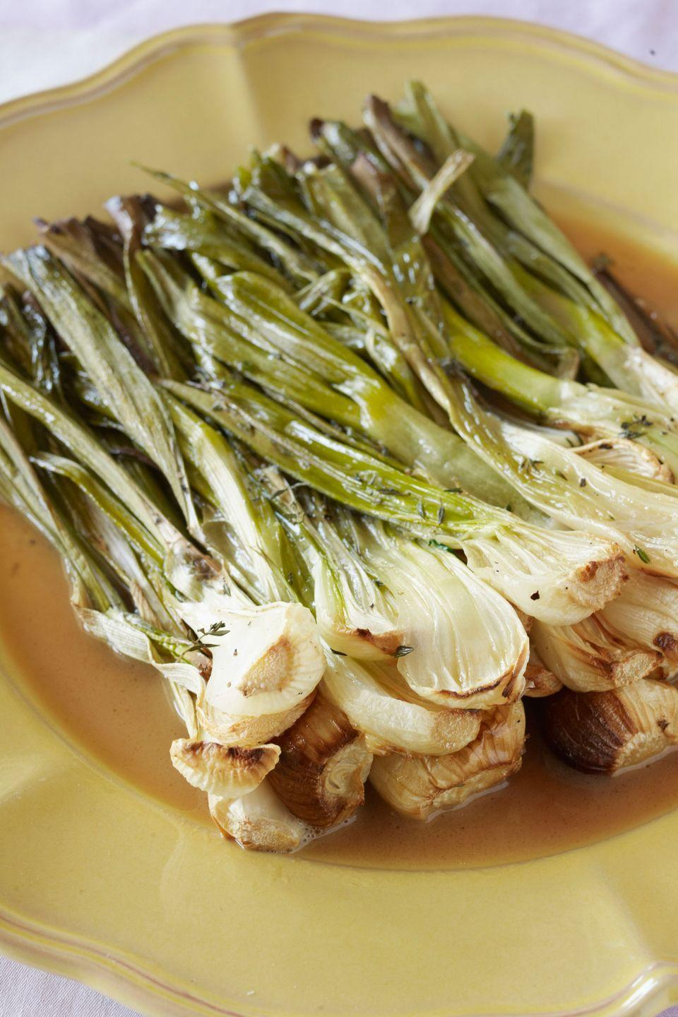 "This fuss-free recipe showcases spring's fresh produce. Baby spring onions are roasted with a little butter and basic seasonings until they become sweet and caramelized. <a href=""https://www.countryliving.com/food-drinks/recipes/a3599/roasted-spring-onions-recipe-clx0411/"" rel=""nofollow noopener"" target=""_blank"" data-ylk=""slk:Get the recipe."" class=""link rapid-noclick-resp""><strong>Get the recipe.</strong></a>"