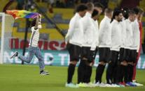 A fan with a LGBT pride flag runs on the pitch during the national anthems before the Euro 2020 soccer championship group F match between Germany and Hungary at the Allianz Arena in Munich, Germany, Wednesday, June 23, 2021. (AP Photo/Matthias Schrader, Pool)