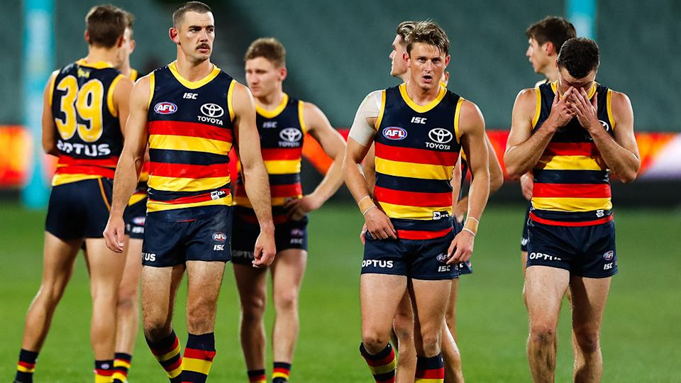 Adelaide Crows players, pictured here walking from the ground looking dejected.