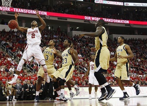 North Carolina State's Lorenzo Brown (2) drives to the basket past Georgia Tech's Marcus Georges-Hunt (3) and Brandon Reed (23) during the first half of an NCAA college basketball game in Raleigh, N.C., Wednesday, Jan. 9, 2013. (AP Photo/Gerry Broome)