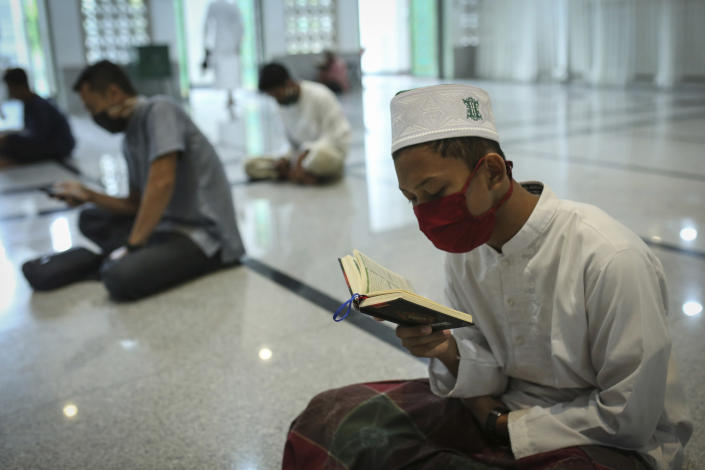 Muslim men wearing face masks as a precaution against coronavirus men read the holy book of Quran during the first day of the holy fasting month of Ramadan at a mosque in the religiously conservative province of Aceh, Indonesia, April 24, 2020. (AP Photo/Heri Juanda)