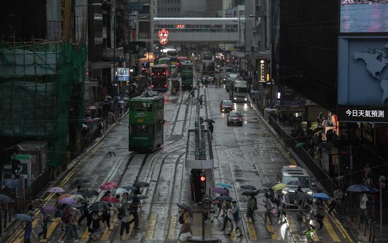 People holding umbrellas cross Des Voeux Road in the Central district in Hong Kong - Ivan Abreu/Bloomberg