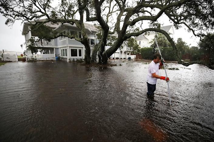 Mike Pollack searches for a drain in the yard of his flooded waterfront home in Wilmington.