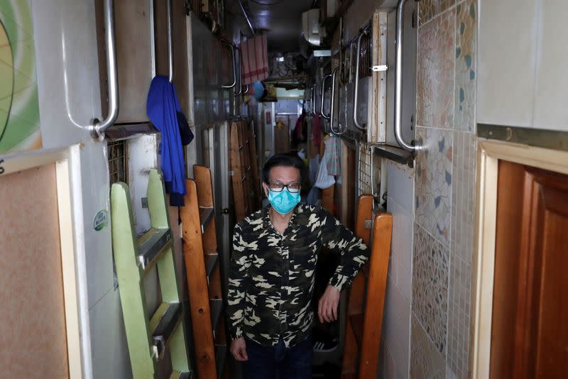 "Simon Wong, 64, poses for a photo outside his 2 square metre subdivided residential unit, known as a ""coffin home"", following the outbreak of the new coronavirus, in Hong Kong"