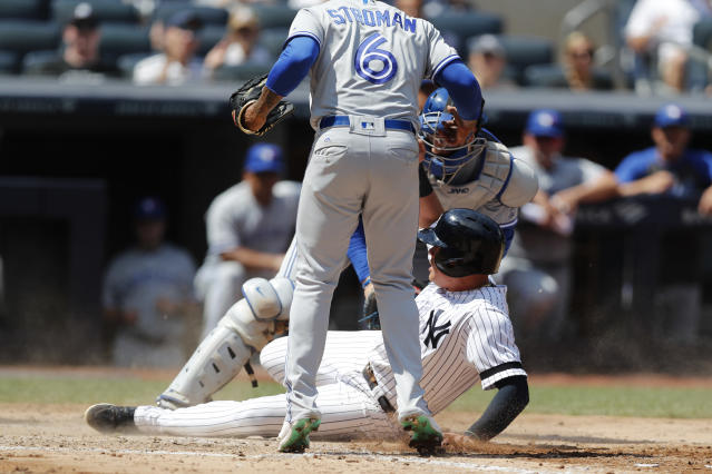 Toronto Blue Jays starting pitcher Marcus Stroman, left, watches as Blue Jays' catcher Danny Jansen, right, watch as New York Yankees' Gio Urshela, center, slides into home plate trying to score on a wild pitch during the fifth inning of a baseball game, Sunday, July 14, 2019, in New York. The play was video reviewed and Urshela was ruled safe after New York Yankees manager Aaron Boone challenged the call on the field. (AP Photo/Kathy Willens)