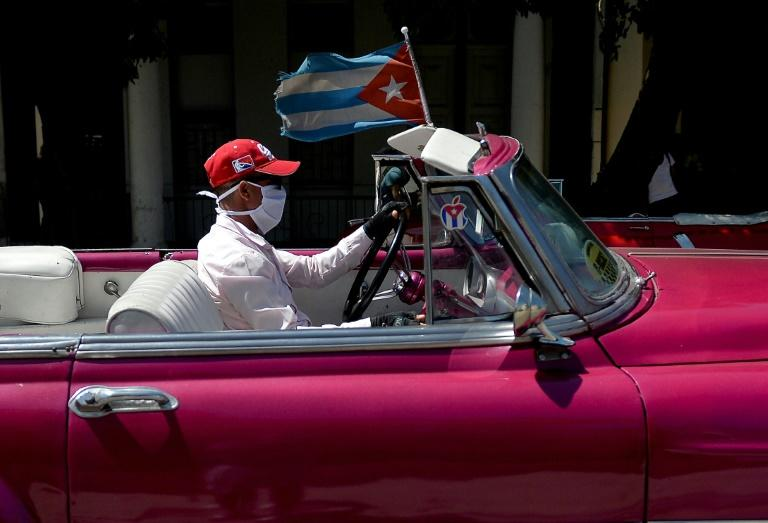 The driver of a vintage American car wears a face mask while taking tourists around Havana -- but Cuba is to close to visitors over the coronavirus outbreak