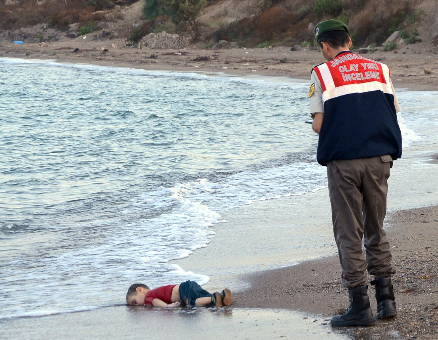 A Turkish paramilitary police officer observes the lifeless body of 3-year-old Aylan Kurdi on a Turkish beach