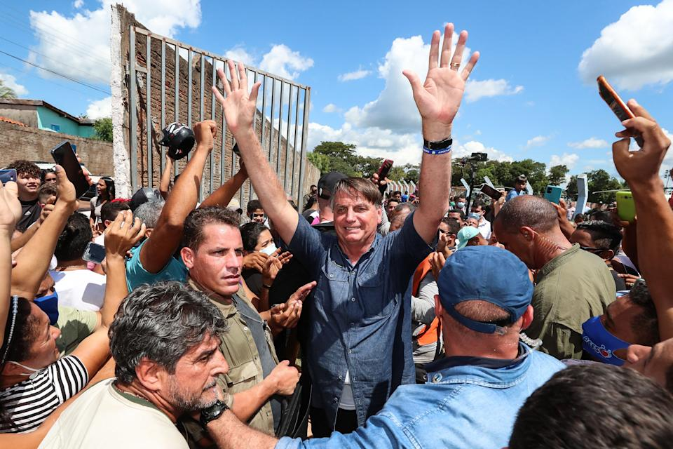 Handout photo released by the Brazilian Presidency of President Jair Bolsonaro greeting a crowd during a non-schedule visit to the city of Senador La Rocque, Maranhao state, Brazil, on May 21, 2021. - Maranhao state Government fined the Brazilian President Jair Bolsonaro after not wearing a face mask and causing an agglomeration during a ceremony held in the municipality of Acailandia. (Photo by Isac NOBREGA / Brazilian Presidency / AFP) (Photo by ISAC NOBREGA/Brazilian Presidency/AFP via Getty Images)