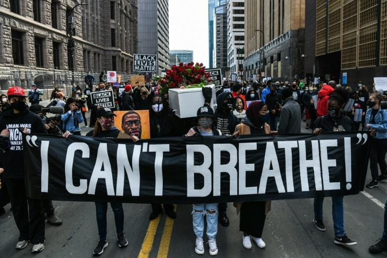 """Demonstrators carry a banner reading """"I Can't Breathe"""" during a March 7, 2021 march in Minneapolis"""