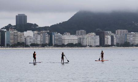People stand up paddleboard at the Copacabana seawaters in Rio de Janeiro