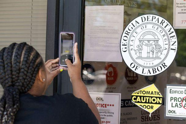 PHOTO: Arnashia McCain uses her phone to copy phone numbers posted on the locked doors of a Georgia Department of Labor office, May 7, 2020, in Norcross Ga. McCain drives for Lyft and has been unable check on the status of her her unemployment claim. (John Bazemore/AP)