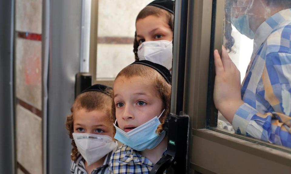 Children watch as Israeli medical workers take swab tests for Covid-19 in Rechovot, in Israel.