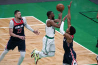 Boston Celtics guard Kemba Walker, center, drives to the basket against Washington Wizards forward Rui Hachimura, right, during the first half of an NBA basketball Eastern Conference play-in game Tuesday, May 18, 2021, in Boston. At left is Wizards center Alex Len. (AP Photo/Charles Krupa)