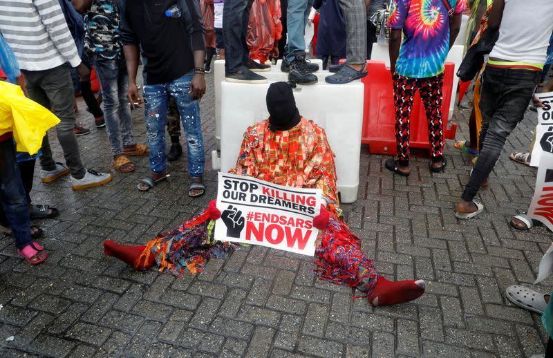 A demonstrator covering his face carries a banner during a protest over alleged police brutality, in Lagos