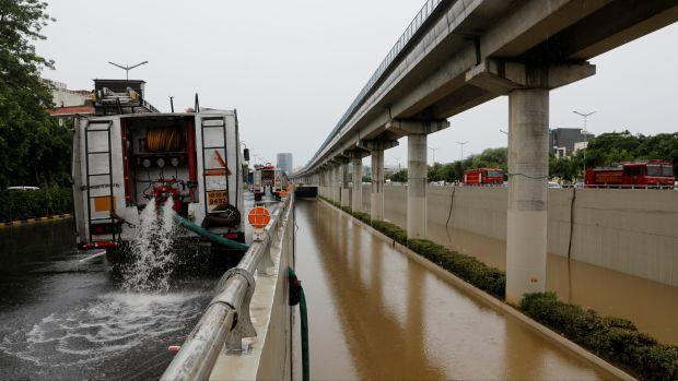 A fire truck pumps out water from a flooded underpass after heavy rains in Gurugram, India, August 20, 2020.