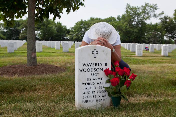 In this undated photo provided by Linda Hervieux, Joann Woodson kneels at the gravesite of her husband Cpl. Waverly B. Woodson Jr. at Arlington National Cemetery in Arlington, Va. Members of Congress on Tuesday, Sept. 8, 2020 said Woodson Jr., a Black army medic who saved dozens of wounded troops on the beaches of Normandy on D-Day despite being severely wounded himself, deserves the Medal of Honor, as they announced legislation to posthumously award it to him.