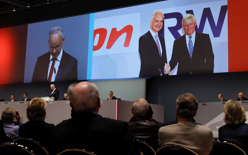 A picture of the handshake of E.ON CEO Johannes Teyssen (L) and RWE CEO Rolf Martin Schmitz, marking the planned merger of the two German utilities, is displayed on a screen as EO.N CEO Teyssen addresses the company's annual shareholder meeting in Essen, Germany, May 14, 2019. REUTERS/Wolfgang Rattay