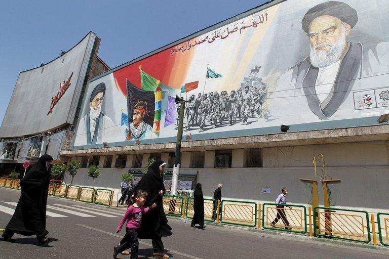 Iranian women walk past a mural depicting Iran's supreme leader Ayatollah Ali Khamenei (L) and late revolutionary leader Ayatollah Ruhollah Khomeini (R) at Enghelab (Revolution) Square in Tehran on April 27, 2012. The Vatican, Iran and other religious states are resisting efforts by a UN conference to demand tougher global standards to prevent violence against women and children