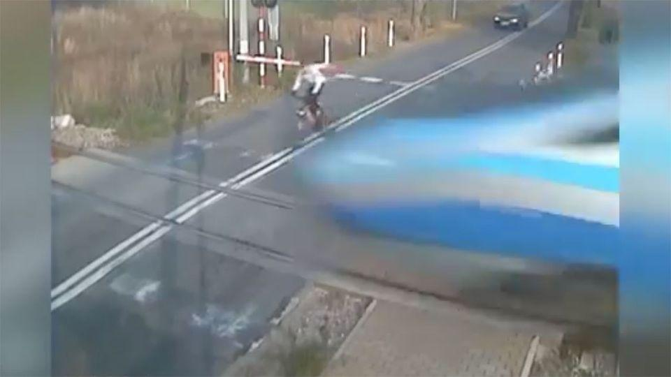The cyclist can be seen approaching the track as a train tears by. Photo: screenshot/Youtube