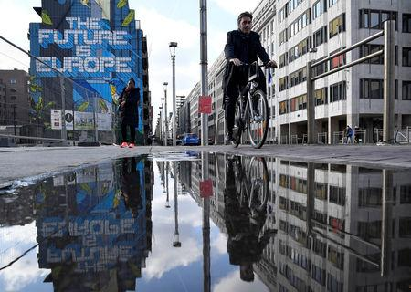 People are reflected in a puddle as they pass by a mural near the EU headquarters in Brussels, Belgium March 20, 2019. REUTERS/Toby Melville