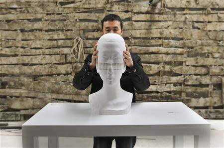 Chinese artist Li Hongbo shows his paper sculpture work, made of 6,000 pieces of paper, while raising it at his studio on the outskirts of Beijing, January 20, 2014. REUTERS/Jason Lee