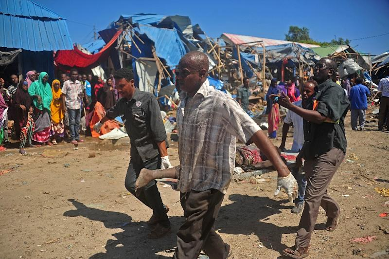 Soldiers assisted by some residents carry the body of a victim from the scene of a suicide car bomb attack at a market in Somalia's capital, Mogadishu on November 26, 2016