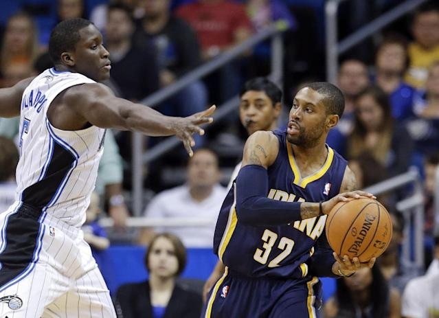 Indiana Pacers' C.J. Watson (32) looks to pass the ball around Orlando Magic's Victor Oladipo, left, during the first half of an NBA basketball game in Orlando, Fla., Sunday, Feb. 9, 2014. (AP Photo/John Raoux)