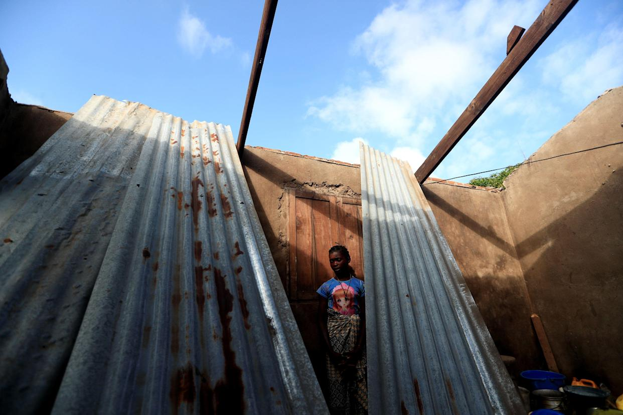 "Luisa Antonio, 14, at her damaged house. ""I would like to be a teacher or a policewoman, but as I don't have a father to help me with the studies, I will stop at grade six and try to get married when I'm 16 years old to escape poverty,"" she said. (Photo: Zohra Bensemra/Reuters)"