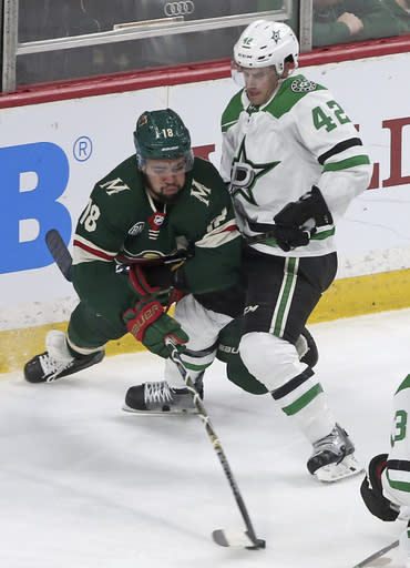 Minnesota Wild's Jordan Greenway, left, tries to get around Dallas Stars' Taylor Fedun to advance the puck in the first period of an NHL hockey game Thursday, March 14, 2019, in St. Paul, Minn. (AP Photo/Jim Mone)