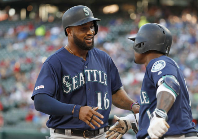 Seattle Mariners' Domingo Santana, left, and Tim Beckham, right, celebrate Santana's solo home run against the Texas Rangers in the first inning of a baseball game in Arlington, Texas, Tuesday, July 30, 2019. (AP Photo/Tony Gutierrez)