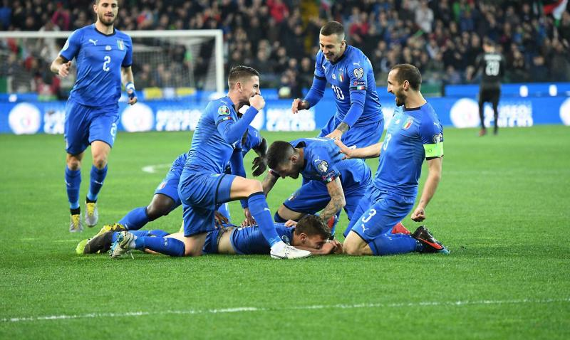 Italy's Nicolo Barella, on ground, celebrates with his teammates after scoring his side's first goal during the Euro 2020 Group J qualifying soccer match between Italy and Finland at the Friuli-Dacia Arena stadium in Udine, Italy, Saturday, March 23, 2019. (Alberto Lancia/ANSA via AP)