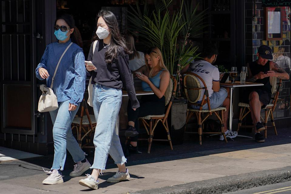People sit at outdoor tables at a restaurant in Soho, in London, on Monday as coronavirus cases hit the highest daily rate since February. (AP)
