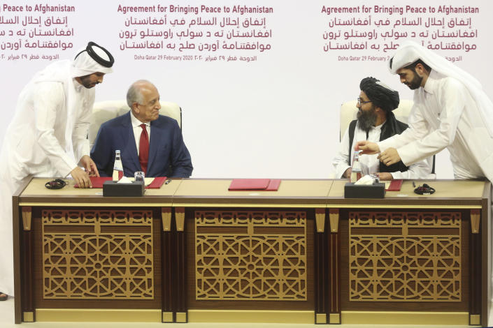 U.S. peace envoy Zalmay Khalilzad, left, and Mullah Abdul Ghani Baradar, the Taliban group's top political leader sign a peace agreement between Taliban and U.S. officials in Doha, Qatar. on February 29, 2020. (Hussein Sayed/AP)