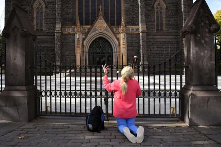 A woman prays outside the shuttered St Patrick's Catholic Cathedral in Melbourne (AFP Photo/William WEST)