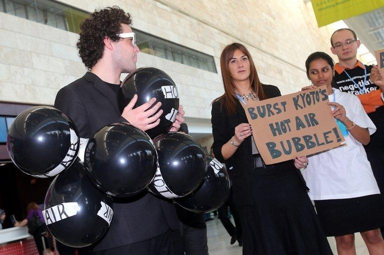 """A man with 13 air filled balloons are pinned to his suit during a small protest outside the United Nations Framework Convention on Climate Change in Doha, on December 4. The latest round of UN climate talks, notorious for dragging out way beyond their scheduled close as negotiators held out to the very last in a poker-like game of oneupmanship, deadlocked on financing and """"hot air"""" carbon credits"""