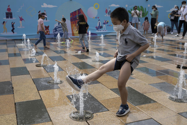 A child wearing a mask to curb the spread of the coronavirus plays with a water fountain on Children's Day in Beijing on Monday, June 1, 2020. (AP Photo/Ng Han Guan)