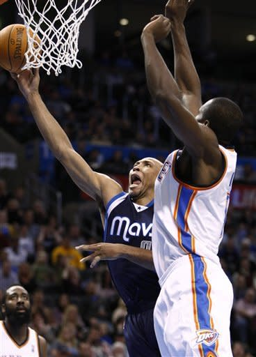 Dallas Mavericks forward Shawn Marion, center, goes up for a basket in front of Oklahoma City Thunder's Serge Ibaka, right, during the first quarter of an NBA basketball game in Oklahoma City, Thursday, Dec. 29, 2011. (AP Photo/Alonzo Adams)
