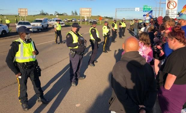 RCMP officers move dozens of protestors to the side of the Trans-Canada Highway at the Nova Scotia-New Brunswick border on the evening of June 23, 2021.  ( Jonathan Villeneuve/CBC - image credit)