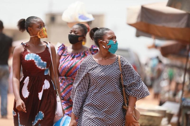 Women wear face masks with kente and wax print designs as they walk through a market.