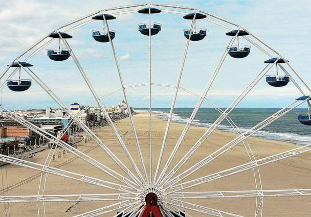 PHOTO: The empty beach stretches out through the spokes of a ferris wheel, April 27, 2020, in Ocean City, Maryland, while closed during the coronavirus pandemic. (Mark Wilson/Getty Images)