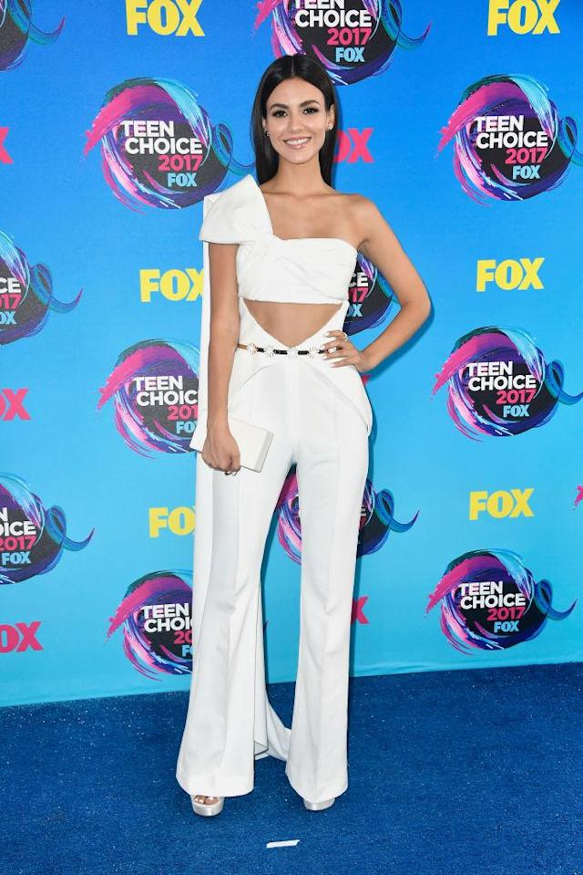 <p>Showing off her arms and tummy, the <i>Victorious</i> star styled her white jumpsuit with a simple white clutch. And let's not ignore that cape! </p>