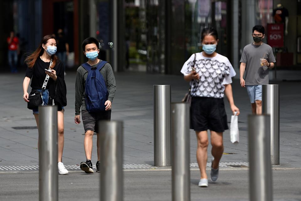 <p>People wearing face masks in Singapore, which has seen a rise in Covid-19 cases</p> (REUTERS)