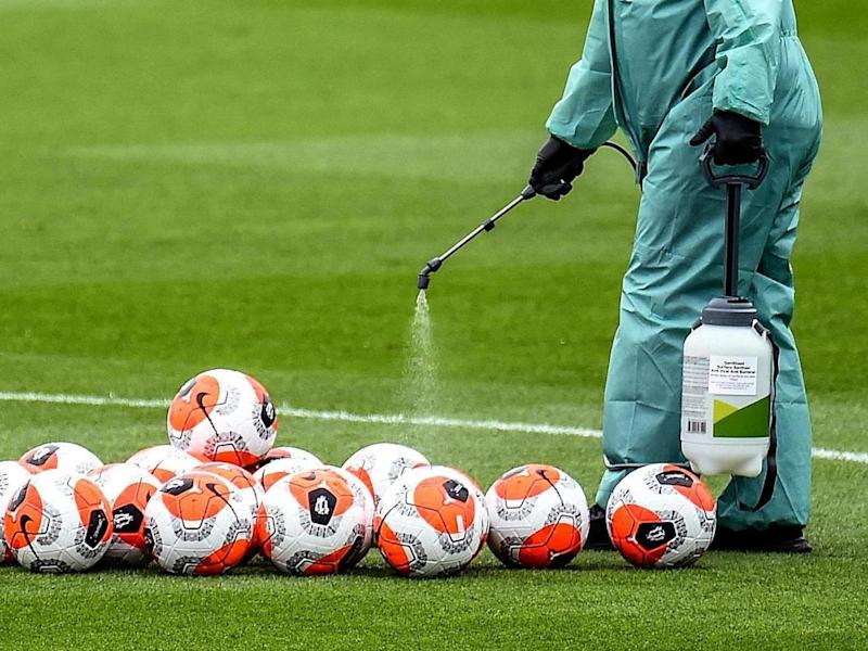 A member of staff at Liverpool's Melwood training ground disinfects footballs: Liverpool FC via Getty Images