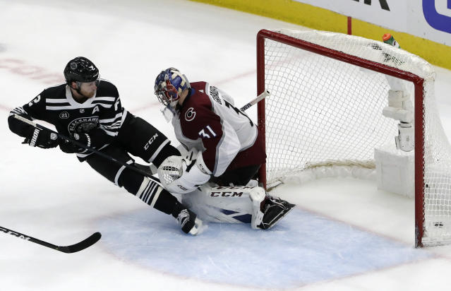 Chicago Blackhawks defenseman Duncan Keith, left, scores against Colorado Avalanche goalie Philipp Grubauer during overtime in an NHL hockey game Sunday, March 24, 2019, in Chicago. The Blackhawks won 2-1. (AP Photo/Nam Y. Huh)