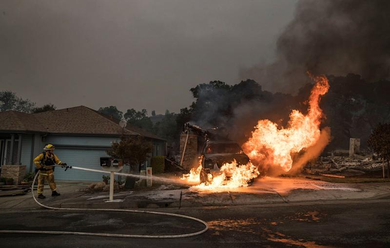 A firefighter puts out a hot spot that flared up in a destroyed neighborhood in Santa Rosa.